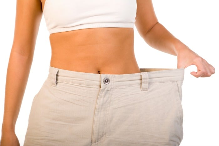 woman pulling out waistband of pants